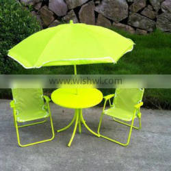 Green color kids table and chair set in garden